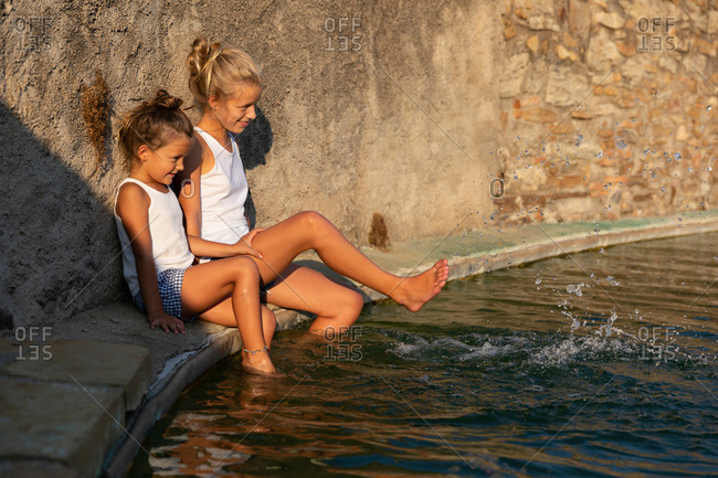 Side view of two girls sitting near shabby wall and splashing clean water of artificial pond on sunny day