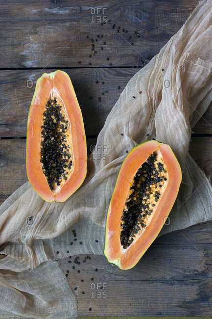 From above composition of ripe juicy papaya fruit with seeds and light grey fabric on wooden background