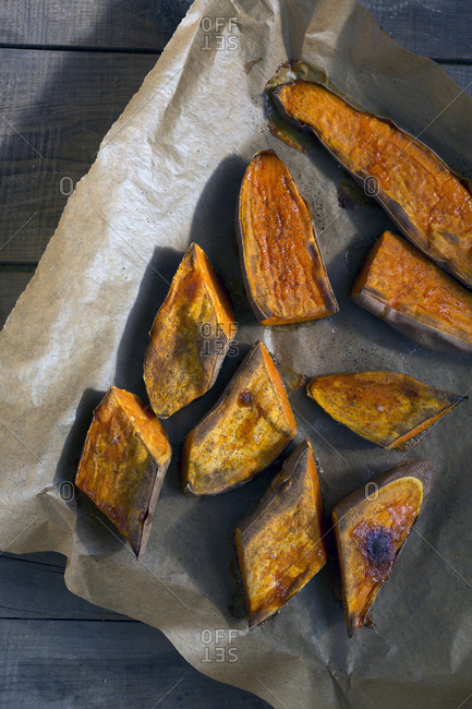 Piece of parchment paper with spoon and pieces of tasty baked Sweet potato placed on wooden table