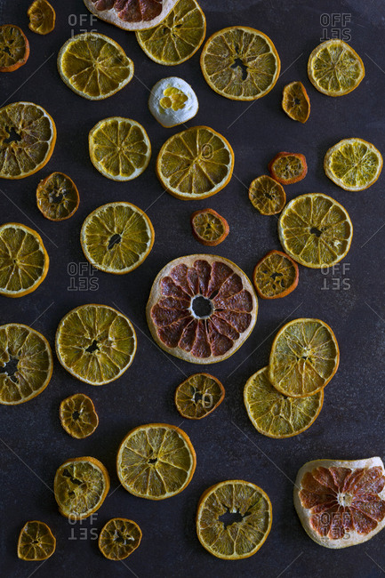 Slices of dried oranges and grapefruits placed on dark gray tabletop