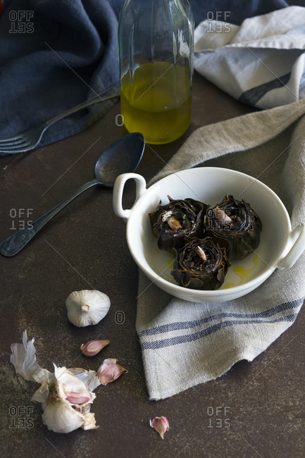 Delicious fried artichokes with aromatic garlic and oil placed in ceramic bowl near napkin and utensils