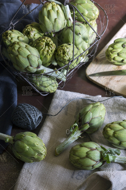 Ripe green artichokes placed on linen fabric on table
