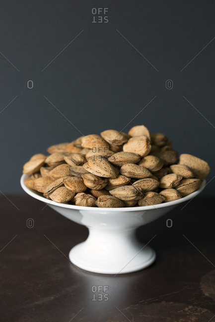 Ceramic bowl full of fresh almonds with shell placed on brown table against brown background