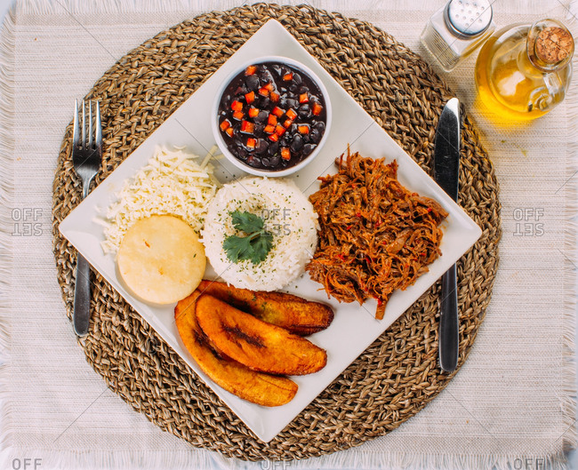 Homemade Venezuelan food. Traditional Venezuelan dish. Pabellon Criollo. White Rice, Black beans, Fried plantains, and Shredded beef