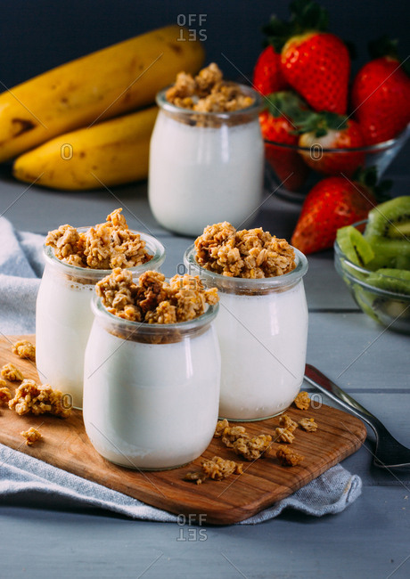 Glass bottles with cold tasty milk and natural delicious walnuts with spoon on wooden tray with fruits