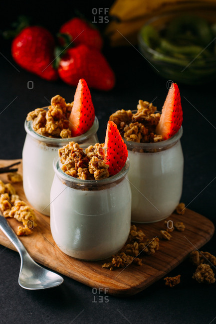 Glass bottles with cold tasty milk and natural delicious walnuts with spoon on wooden tray with strawberries on top