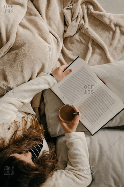 Unrecognizable woman sitting on the bed reading a book and drinking coffee