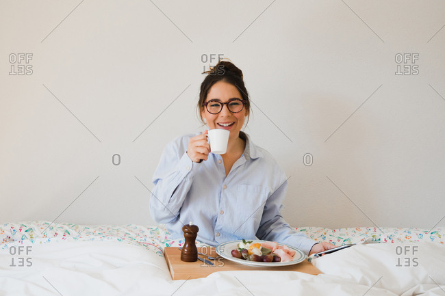 Portrait of cheerful woman sitting on bed with cup in hands and tray with healthy food on legs while using a smart phone