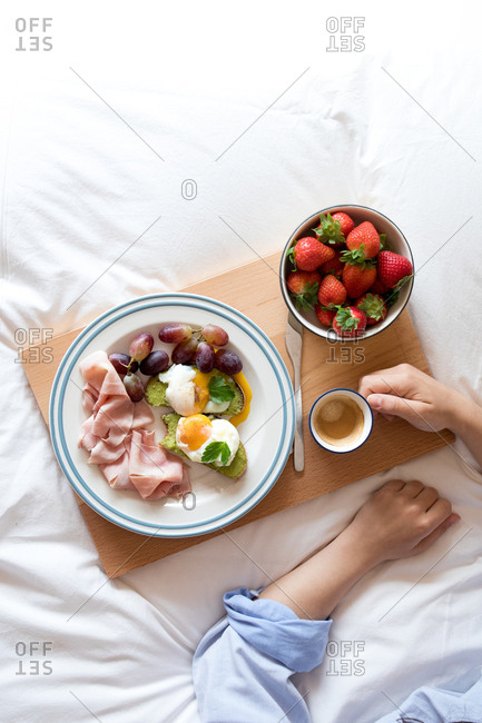 From above crop view of anonymous woman taking a tasty appetizing nutrient breakfast served on bed