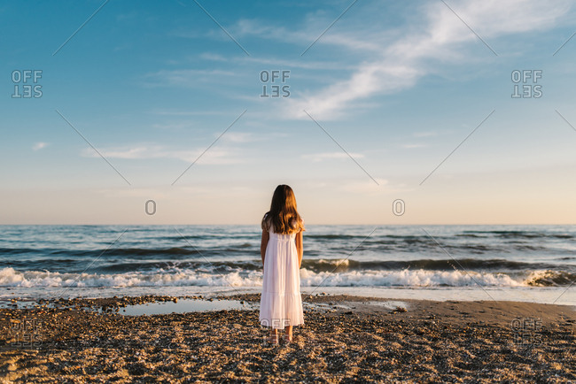 back view of cute female child in white dress standing on sandy seashore