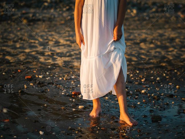 crop little girl in white dress walking on seashore on background of sunshine