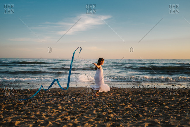 Little girl in white dress running along seashore and holding long blue band on background of evening sky