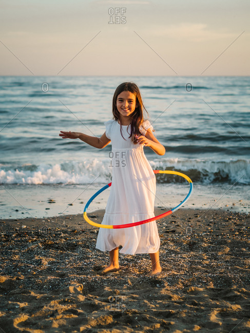 Little girl in white dress playing along seashore with hula hoop on background of evening sky