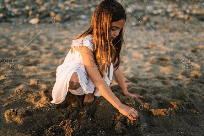 Cute pensive female kid in white dress playing with sand on seaside in sunlight