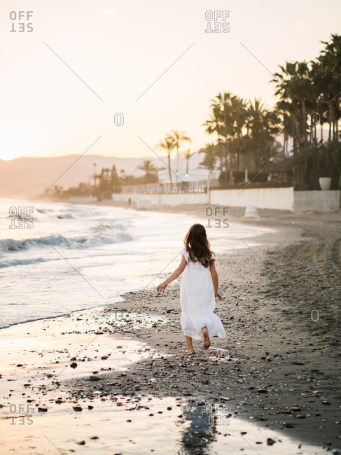 little girl in white dress walking on seashore on background of sunshine
