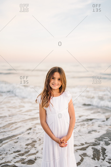 Portrait of charming little girl in white dress standing in water on sandy beach and looking at camera