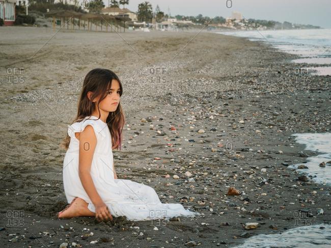cute female child in white dress sitting on sandy seashore