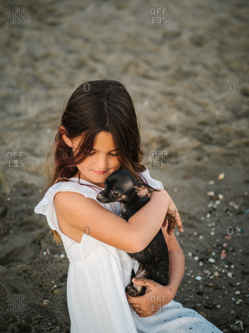 Portrait of charming female child in white dress holding little dog while sitting on sand and smiling