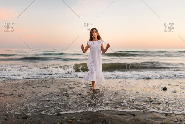little girl in white dress walking and playing on seashore on background of sunshine