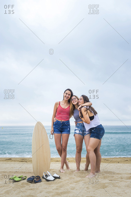 A group of three female friends standing on the beach looking to camera