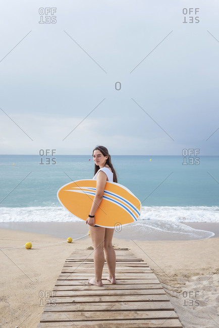 Back view of a teenage girl standing on the beach looking back and holding a surfboard