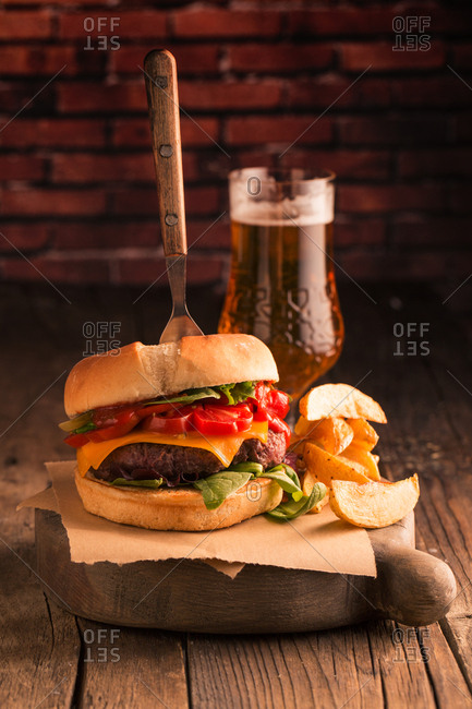 Homemade deluxe burger with cheese, lettuce, tomato and pickles on dark moody background