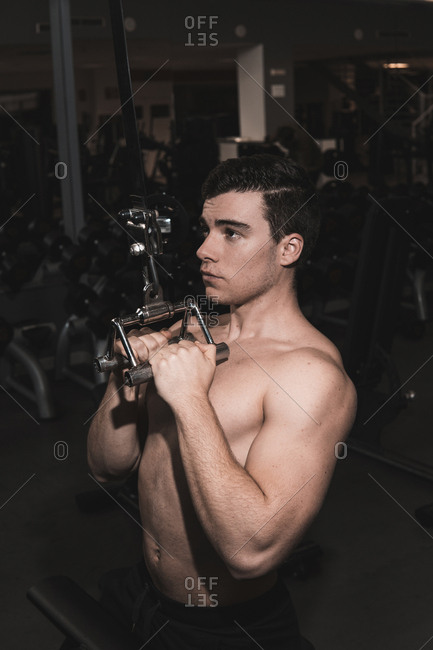 young fitness man doing machine weights in the gym