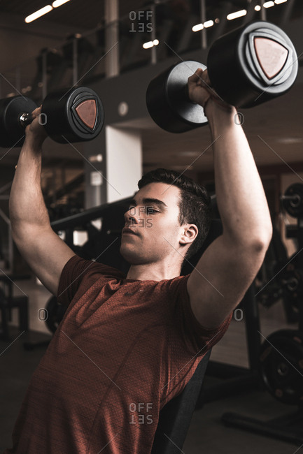 young fitness man doing weights