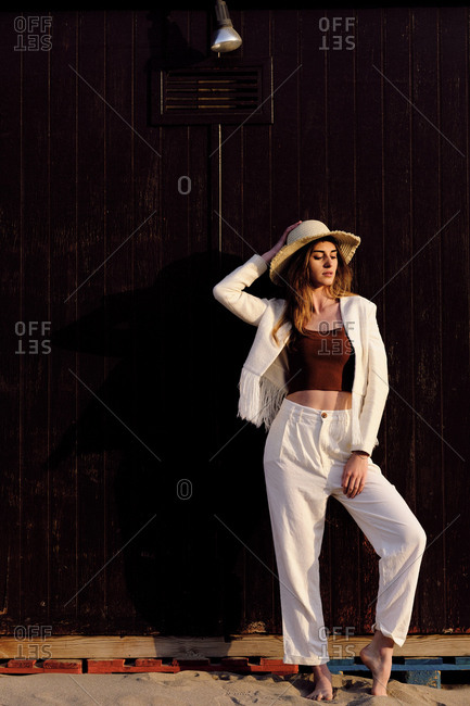 A long hair fashion model with a hat at the beach with a dark background