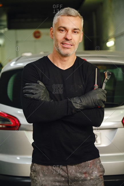 Positive adult male with tools keeping arms crossed and looking at camera while standing near car in garage