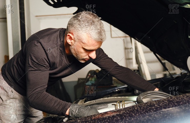 Adult man in gloves repairing engine of vehicle while working in garage