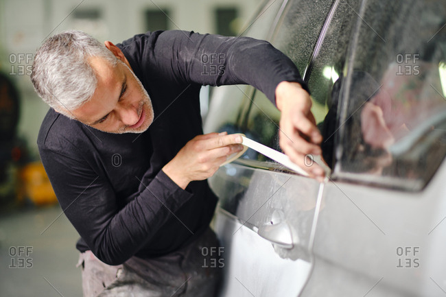 Adult male sticking protective tape on window of modern car while working in garage