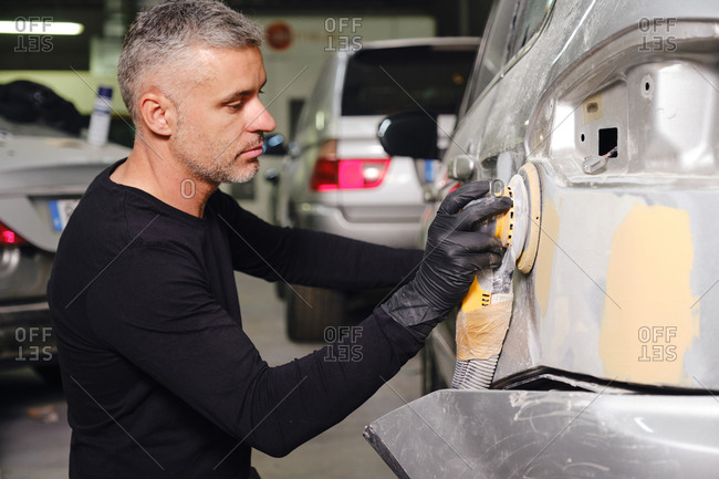 Adult man in dirty outfit looking at camera while removing old paint from car part while working in garage
