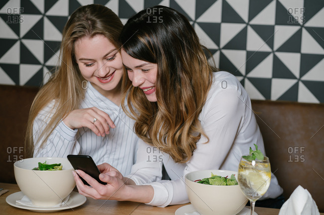 Elegant women friends using phone while sitting at table of restaurant during lunch