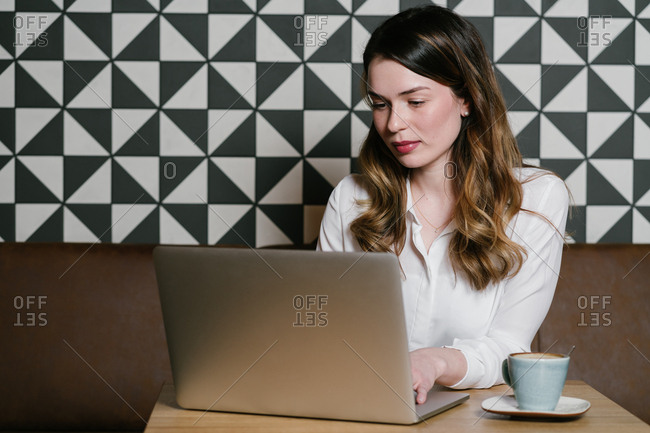 Female freelancer browsing modern laptop while sitting at table with a cup of coffee in cozy restaurant