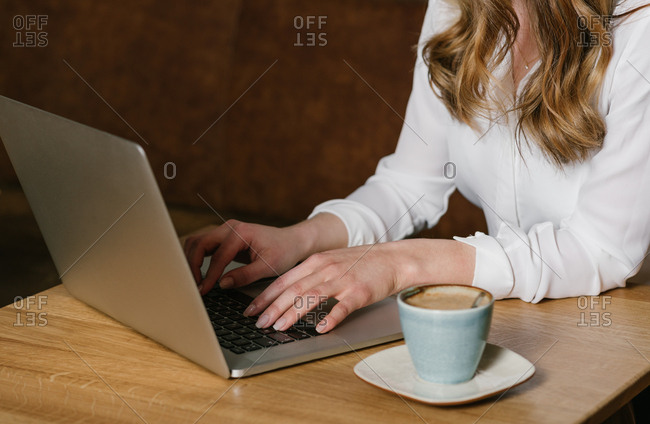 Crop view of anonymous female freelancer browsing modern laptop while sitting at table with a cup of coffee in cozy restaurant