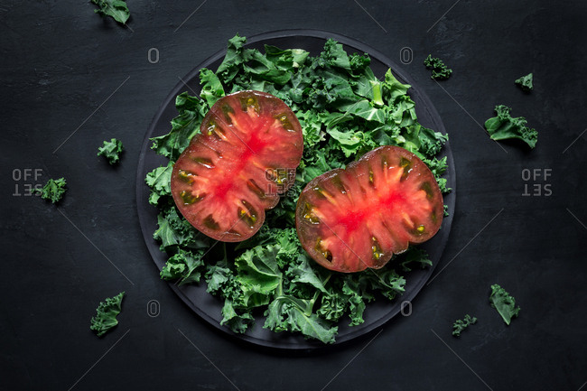 Slices of fresh tomatoes and torn lettuce leaves placed on plate against black plaster background