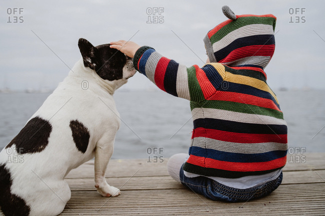 Back view of unrecognizable kid in striped jacket patting spotted French Bulldog while sitting on lumber pier near sea