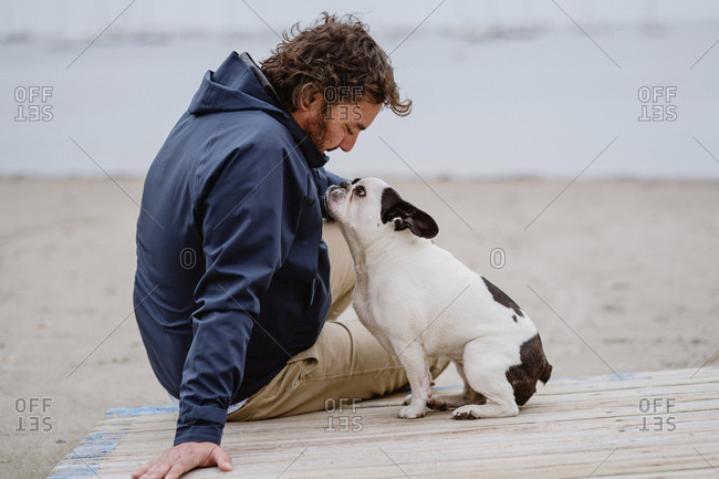 Adult male in warm jacket embracing spotted French Bulldog while sitting on wooden pier and admiring view of rippling sea on dull day