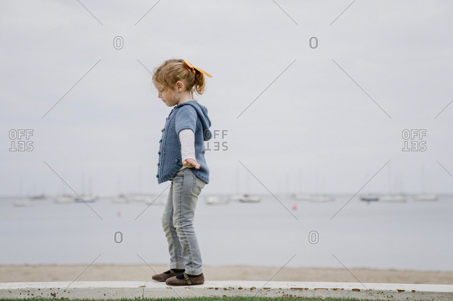 Side view of little girl with outstretched arms walking on border against calm sea and gray sky