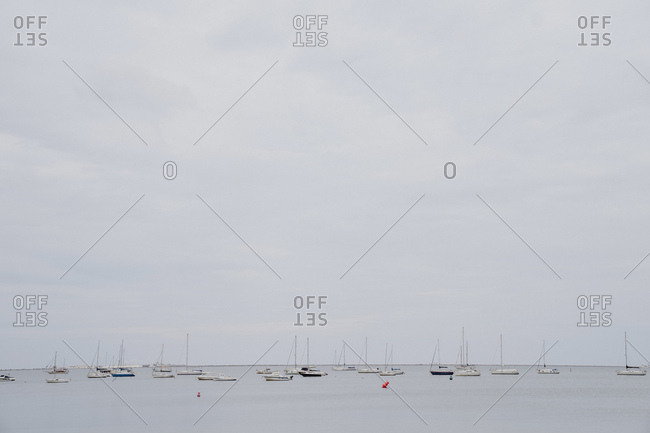 Many sailing boats floating on calm sea water against gray cloudy sky on dull day in port