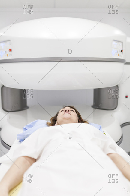 middle-aged woman on an open MRI machine waiting for the test to begin