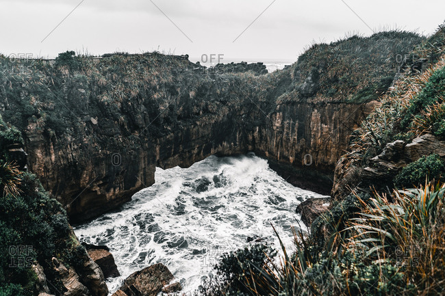 From above landscape of water flowing among cliffs in sea on cloudy day