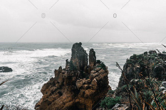 Beautiful landscape of cliffs among sea waves on cloudy day