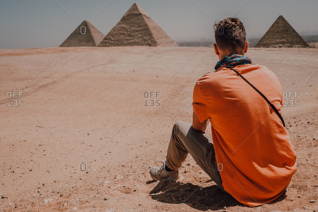 Confident male traveler sitting in desert against famous Great Pyramids in Cairo, Egypt