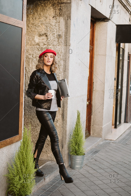 Stylish young female in red beret holding takeaway beverage while walking out a coffee shop on city street