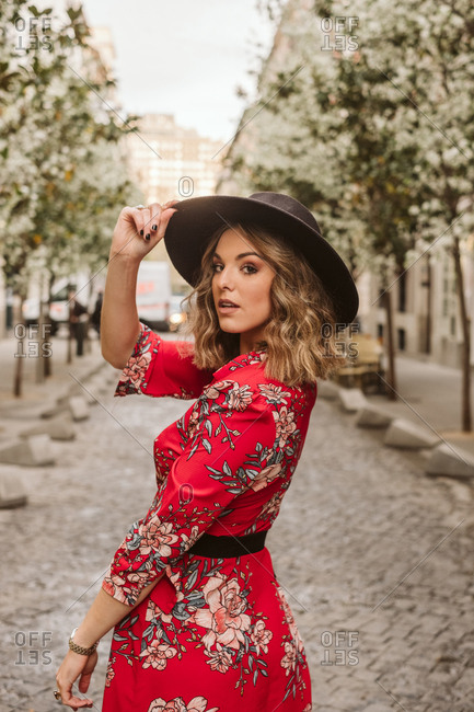 Back view of young woman in stylish dress and hat looking at camera over shoulder while walking on aged pavement on city street
