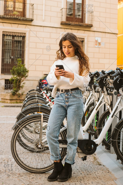 cheerful young female in casual outfit sitting on rental bicycle on sharing station and looking at camera on city street