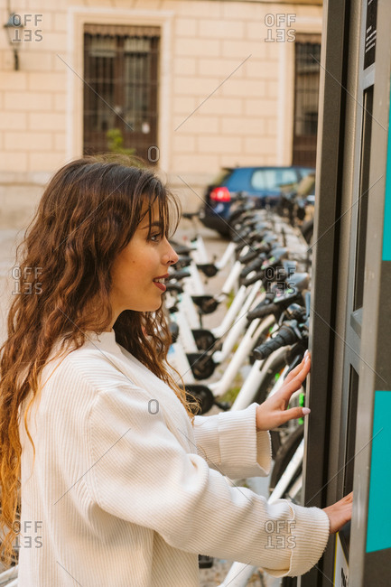 Side view of young lady in casual outfit using kiosk on bicycle sharing station on city street