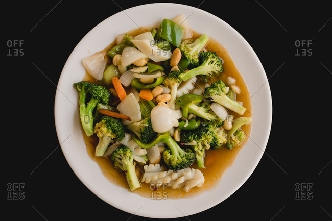 From above prepared tasty hot soup with squid and healthy vegetables like broccoli, carrot, onion, cucumber on black background